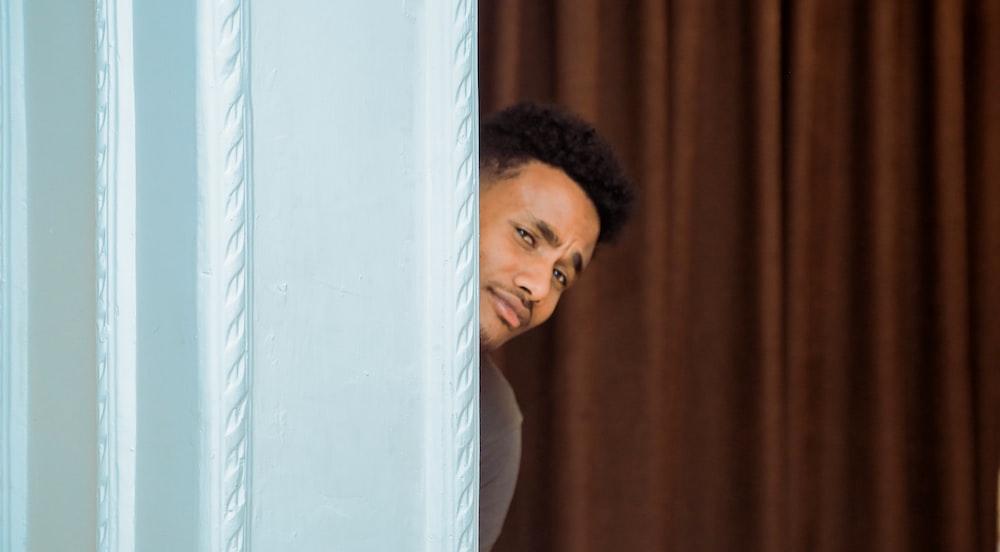 man hiding behind the curtain