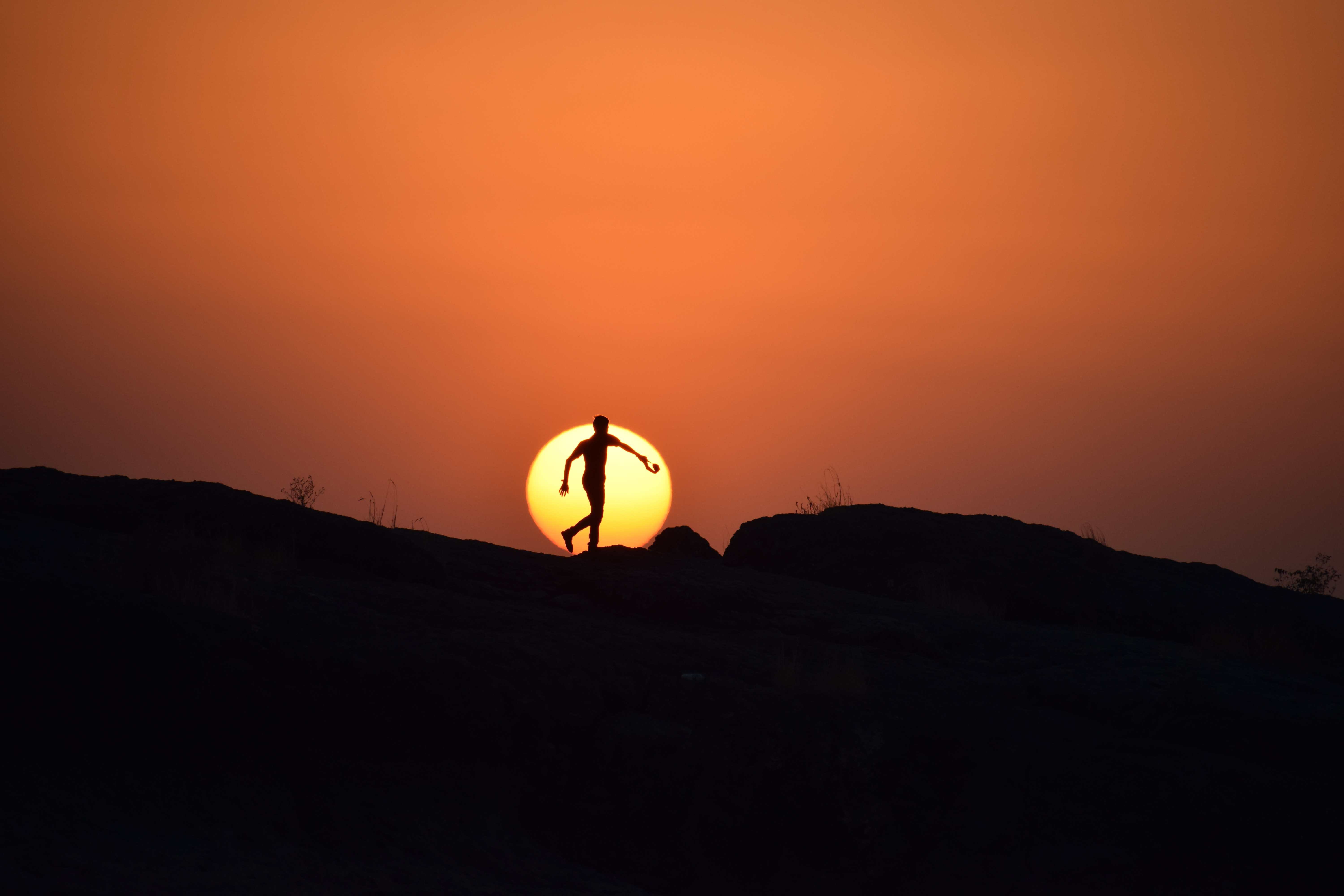 silhouette of man on hill