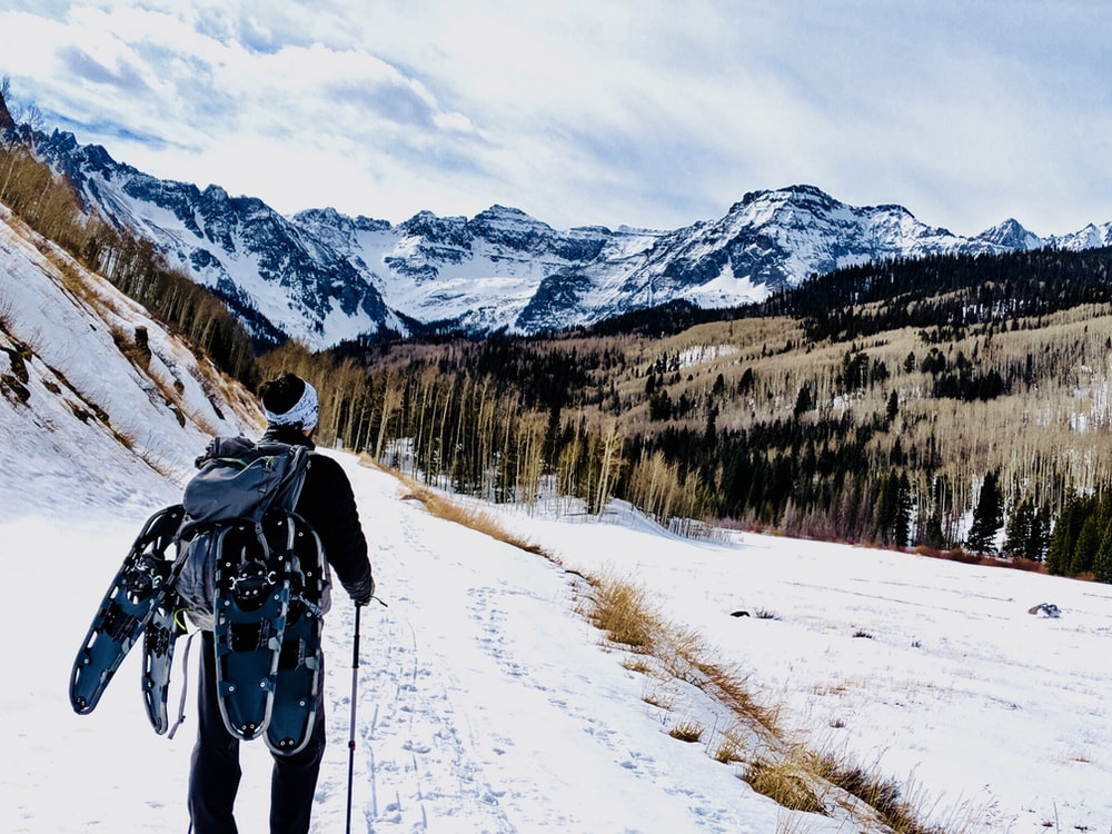 man wearing backpack on snow