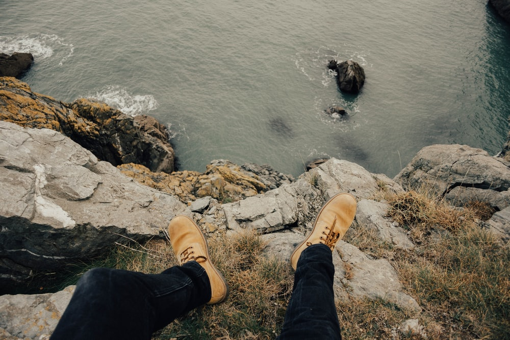 person wearing brown work boots sitting on cliff