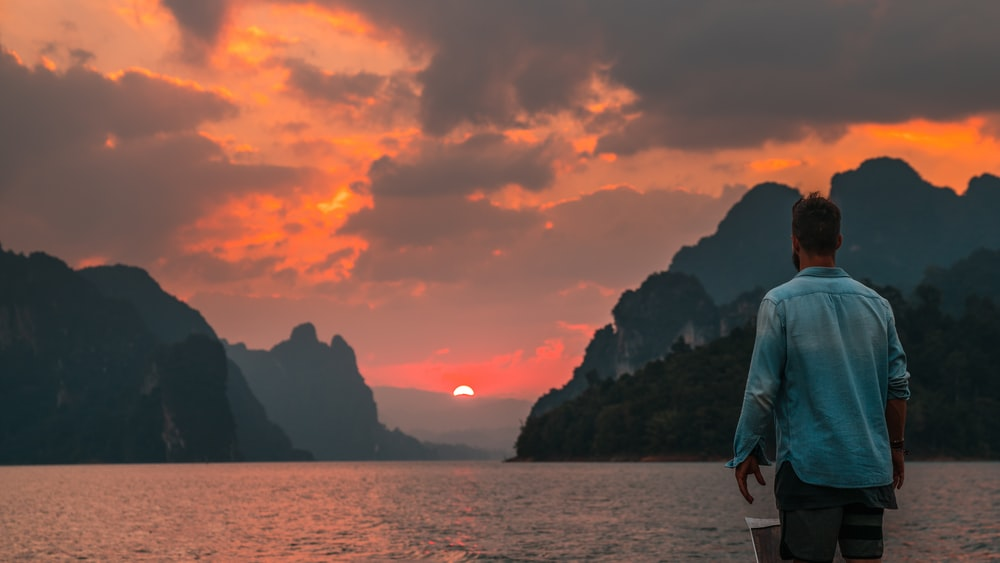 man standing near edge facing body of water during sunset