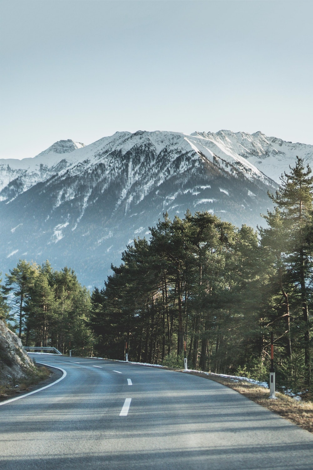 asphalt road beside of green trees in front of mountain covered of snow during daytime
