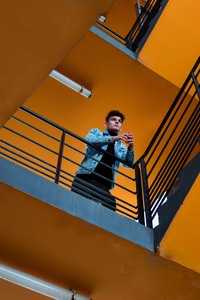 low-angle photography of man standing by the stair railing