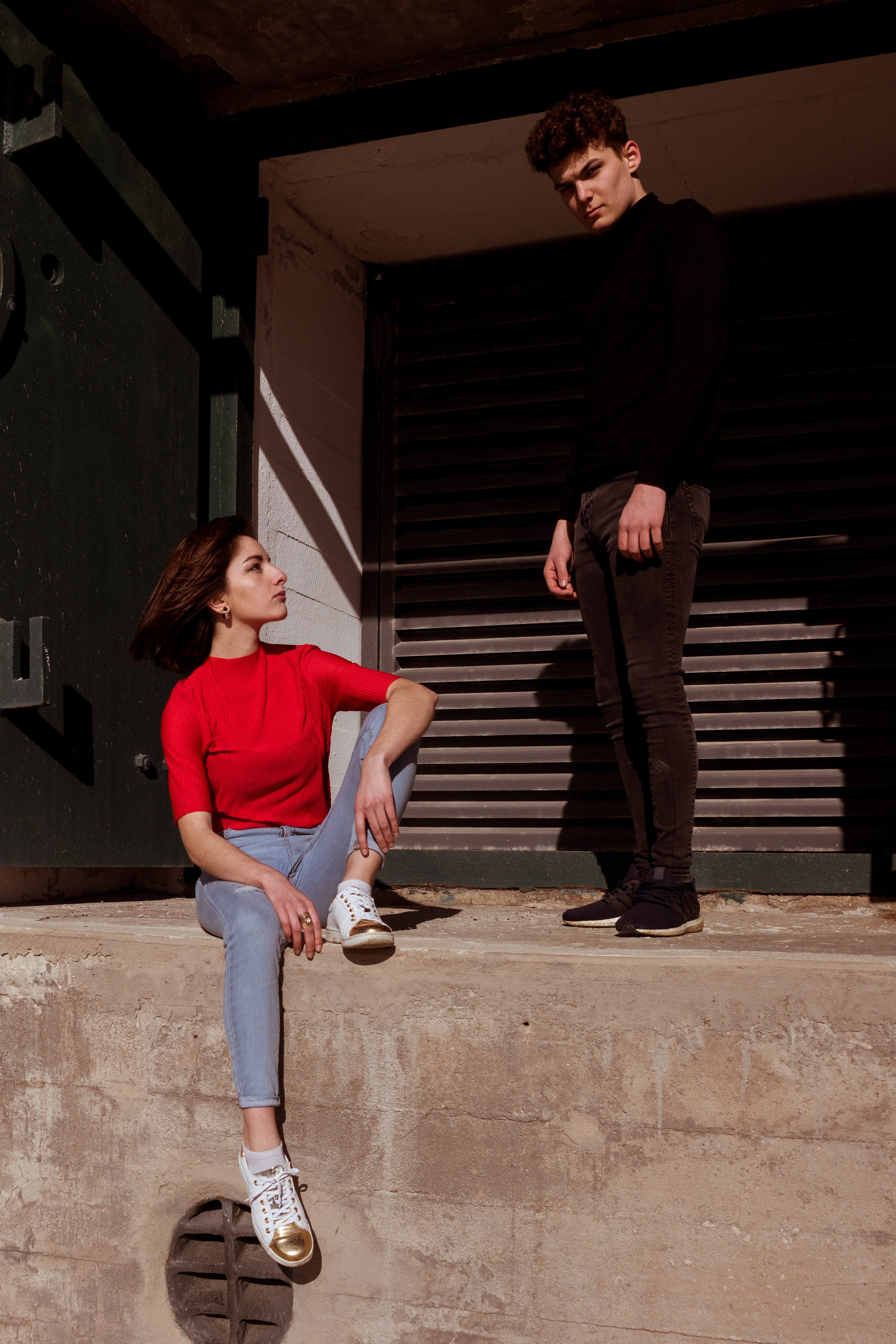 man standing beside woman sitting on concrete wall