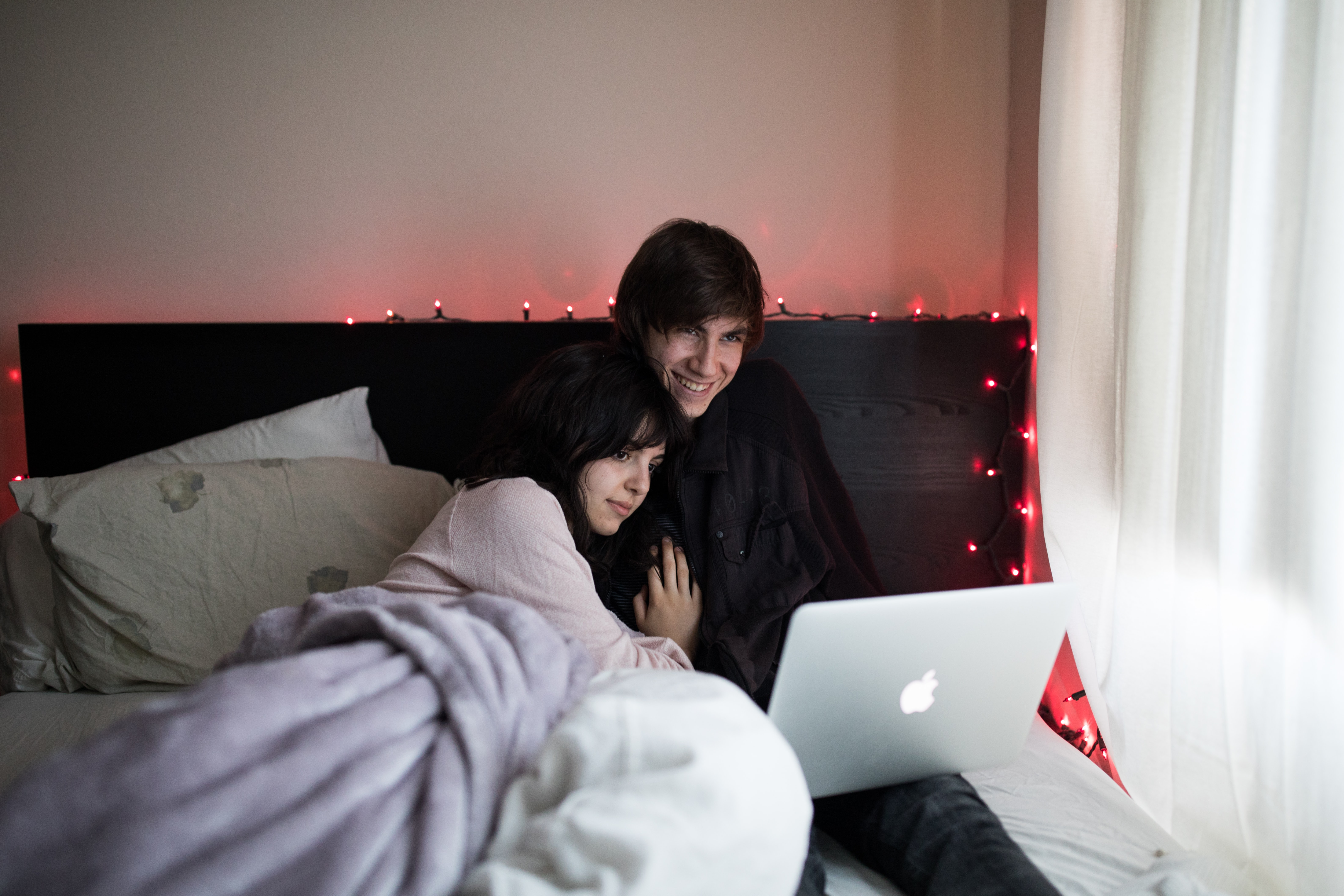 couple on bed using MacBook Air beside of window with white curtain