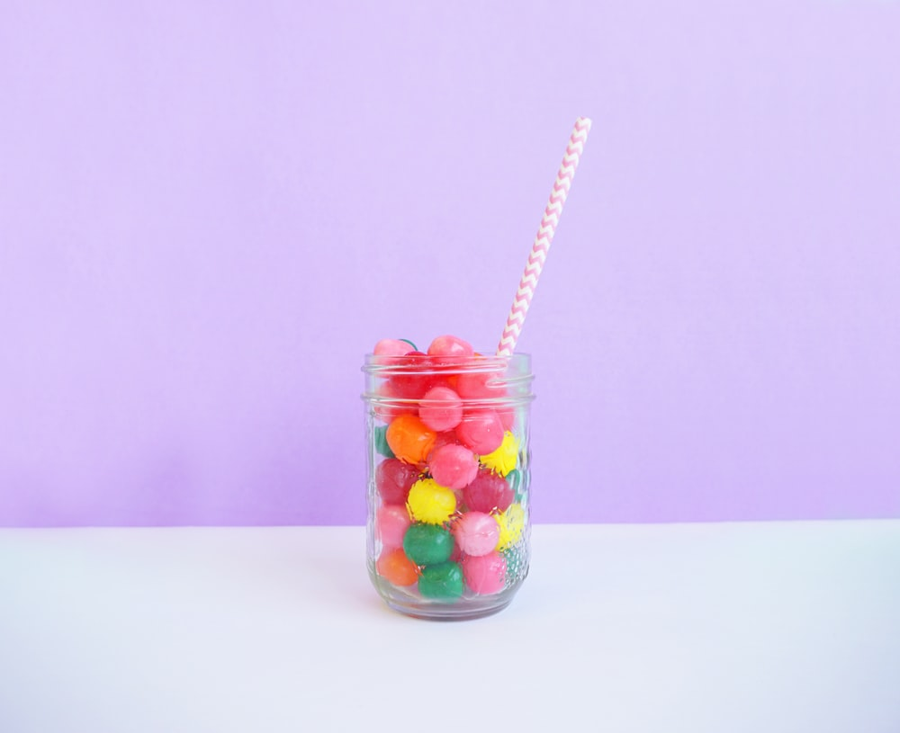 clear beverage jar wit straw on table