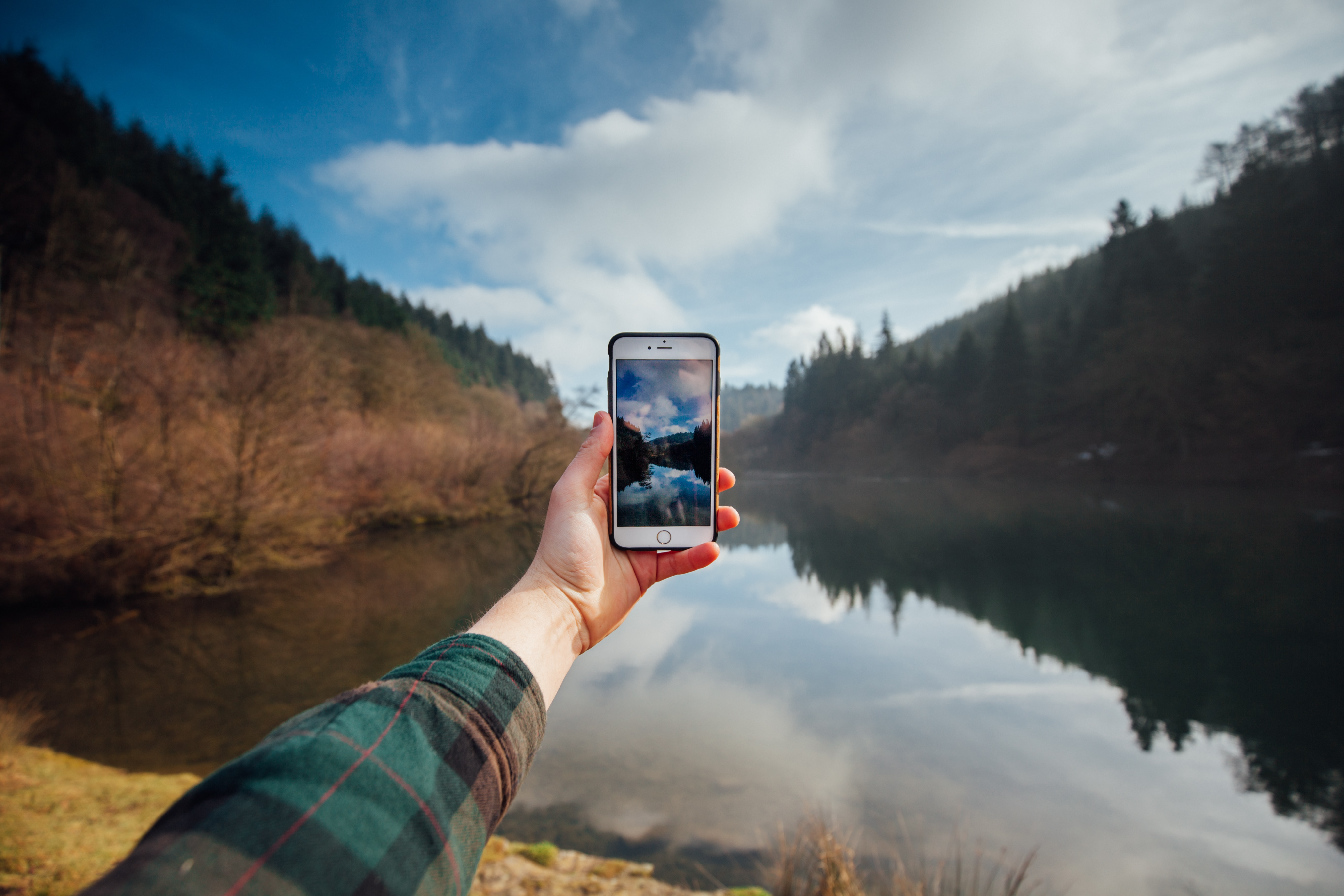 person holding iPhone while taking picture of mountains and body of water during daytime