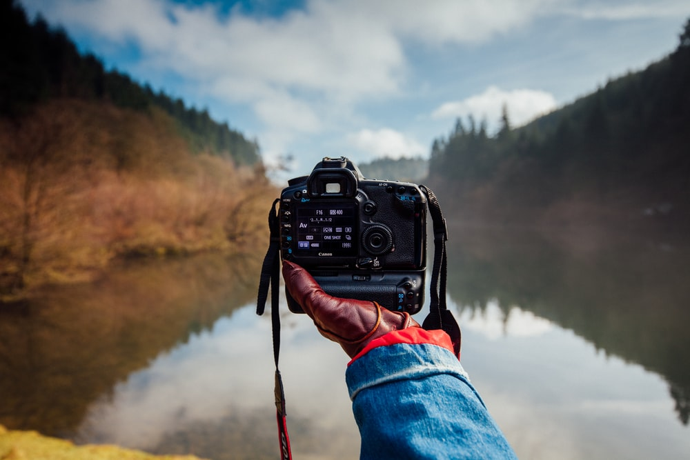 person holding camera facing a river