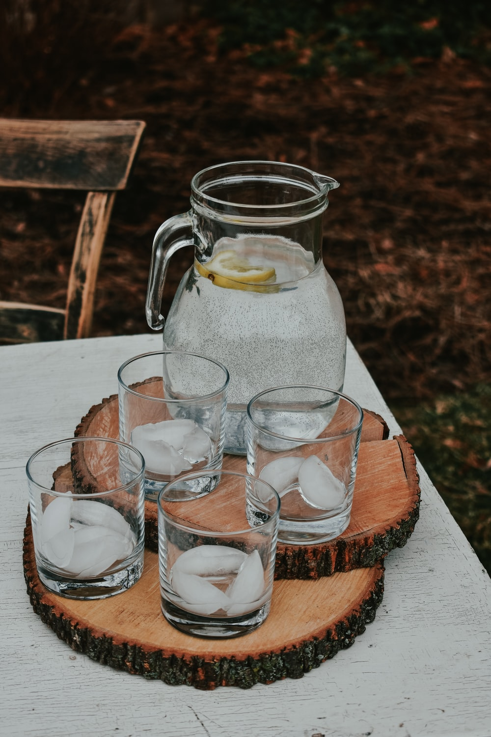lemon juice pitcher with four drinking glasses on top of table