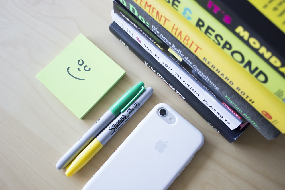 two Sharpie markers beside iPhone and sticky notes