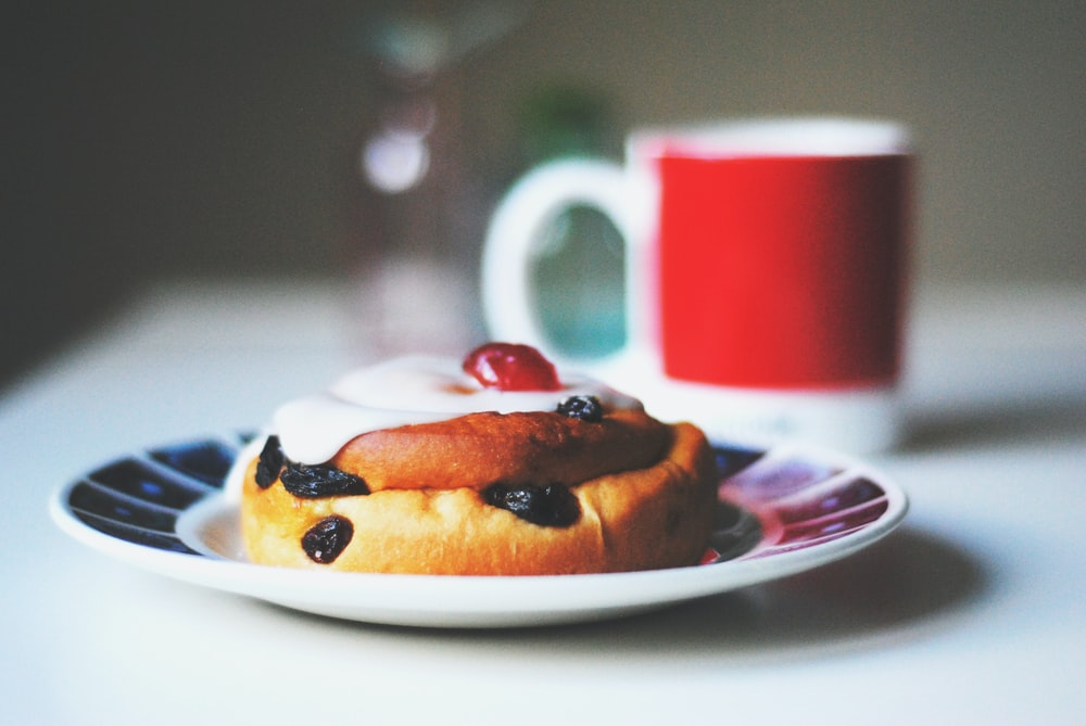 bread with raisins on saucer beside white and red mug