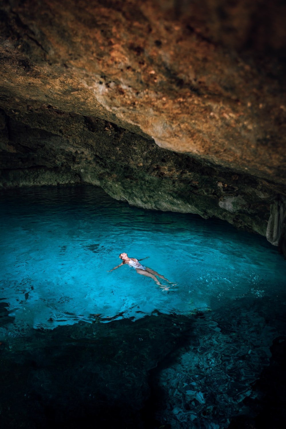 woman swimming under cave