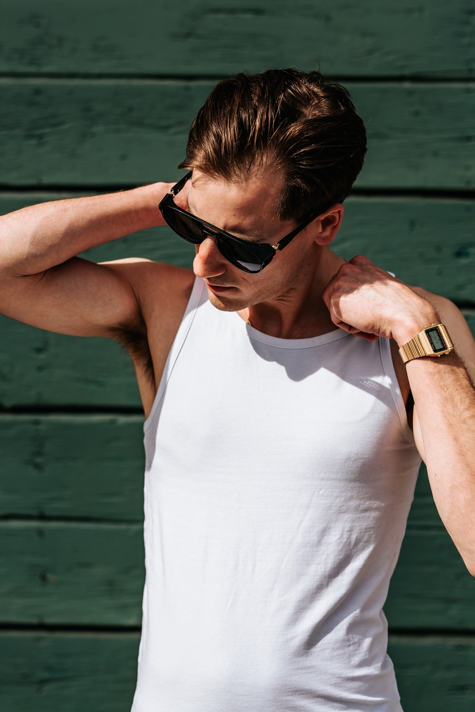 man holding his shoulder wearing eyeglasses