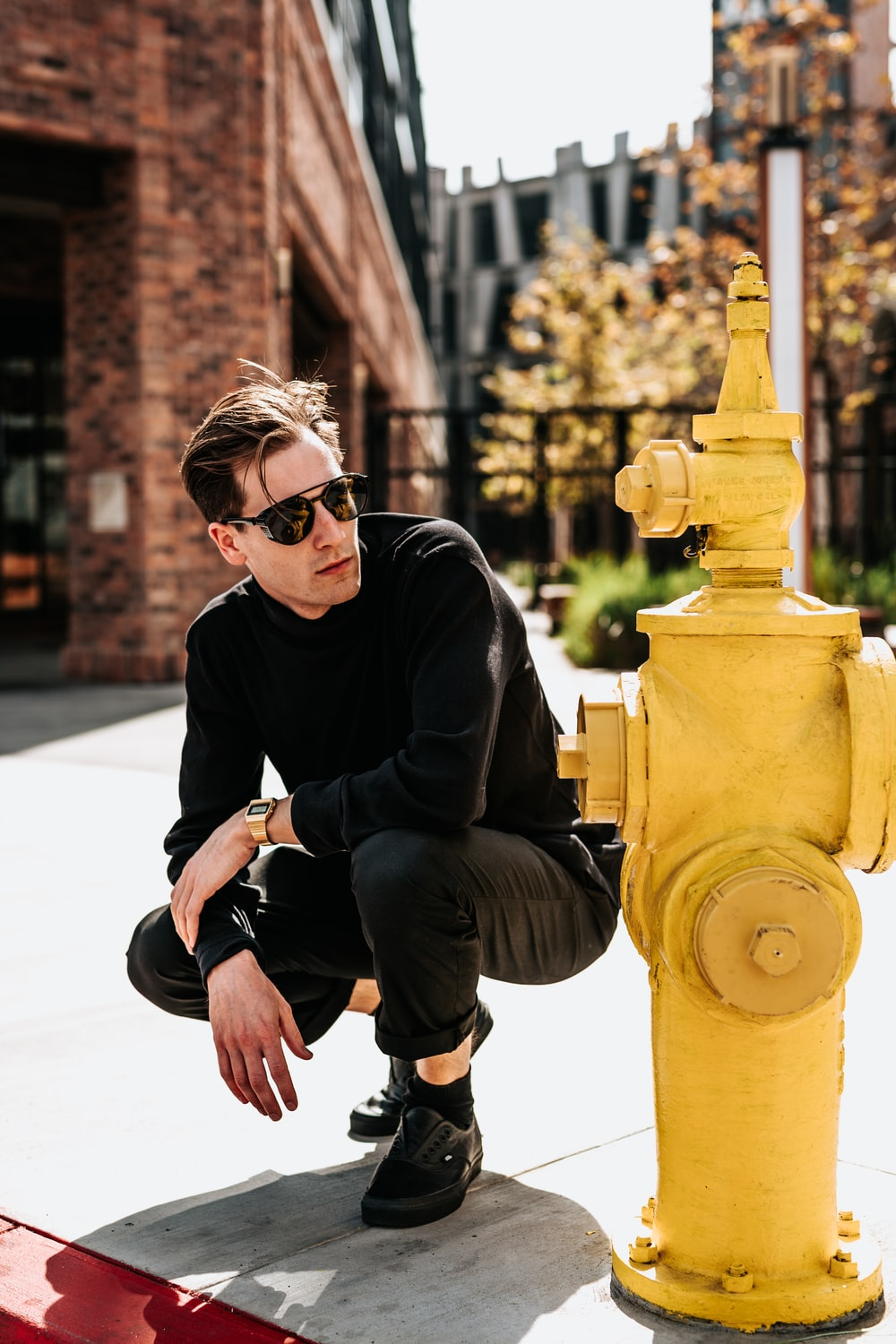 person posing beside fire hydrant