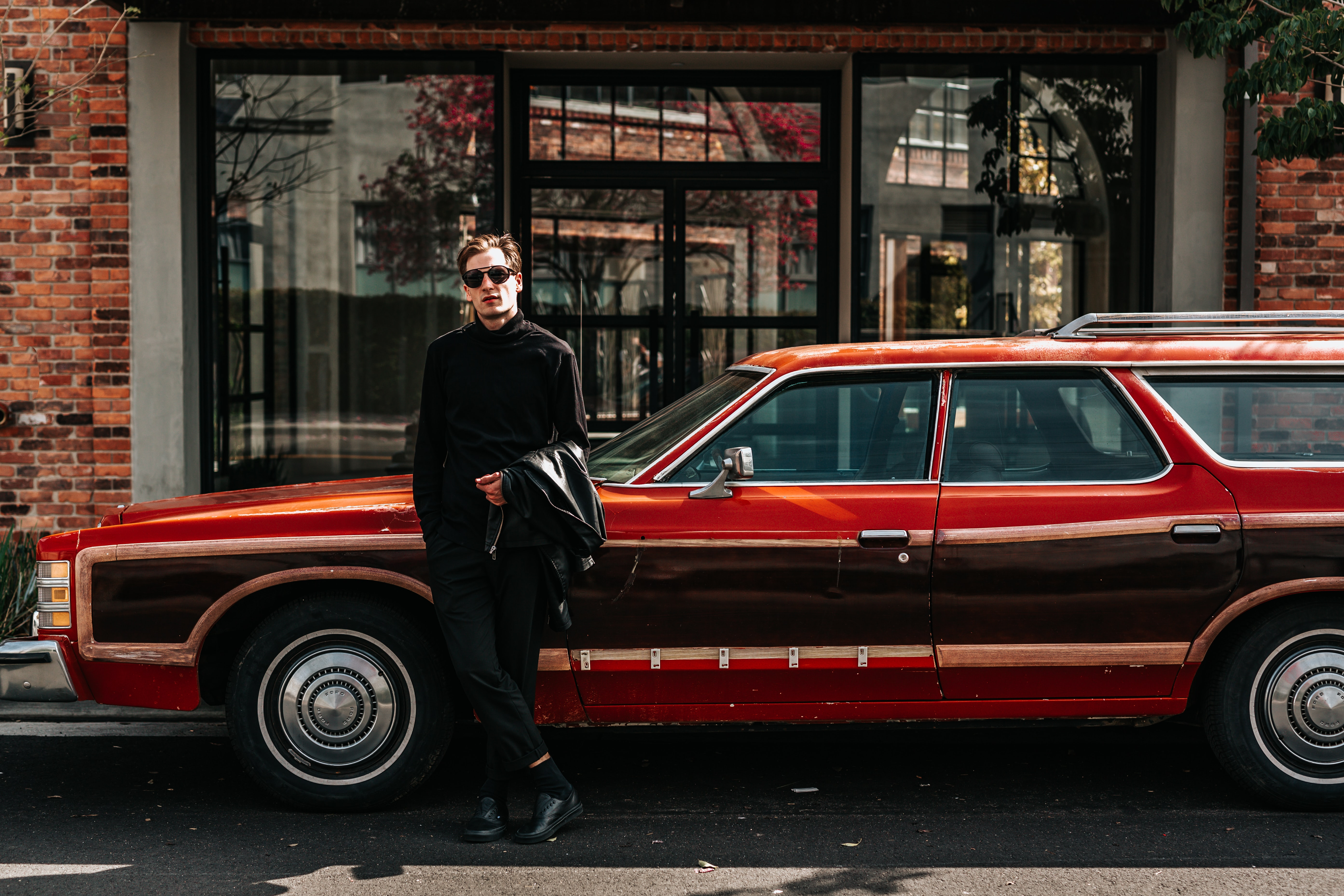 man leaning on station wagon