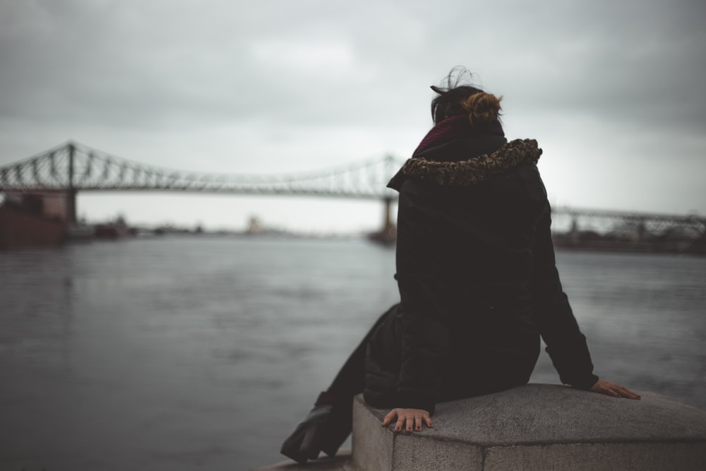 woman sitting on gray concrete table near body of water overlooking bridge