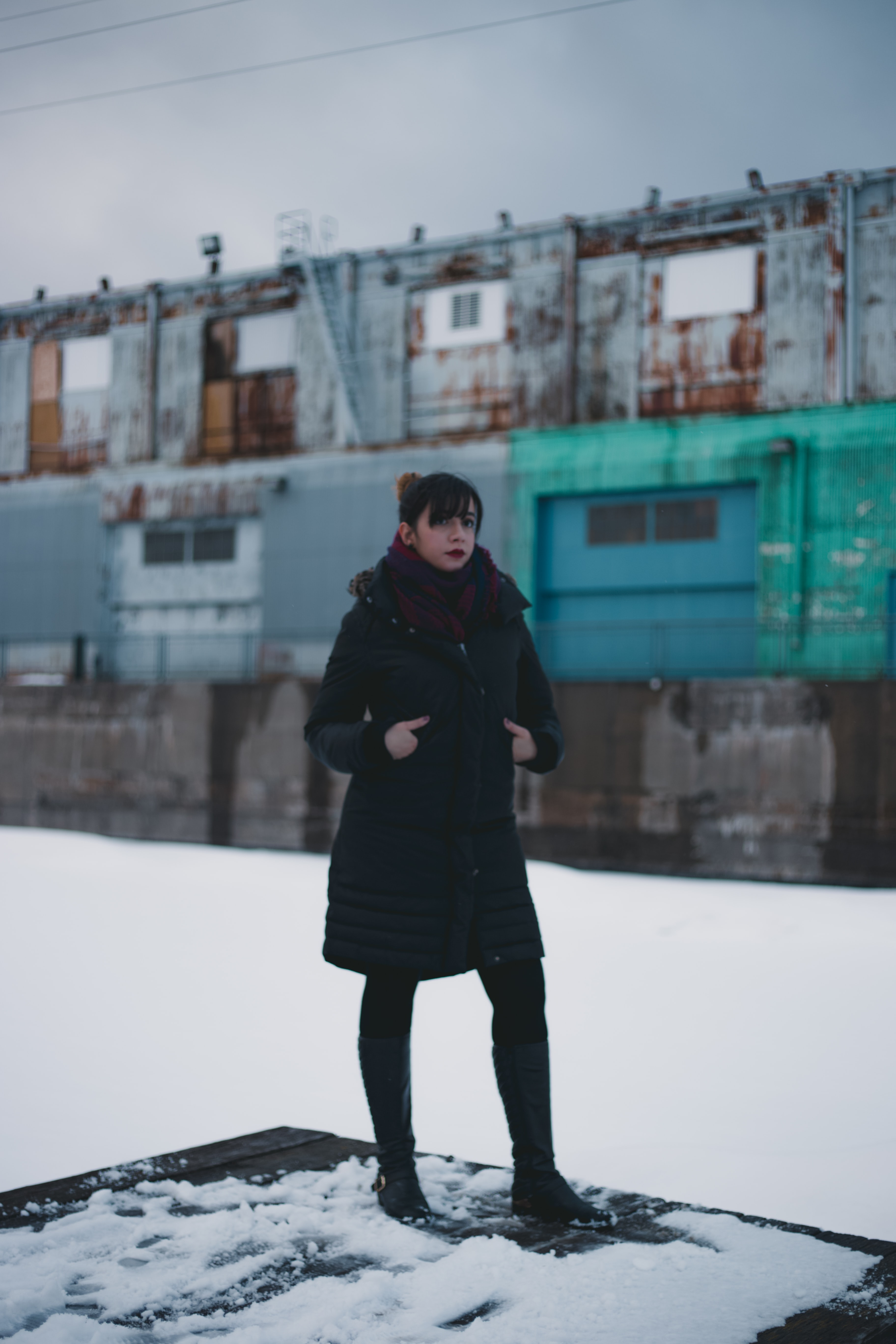 selective focus photography of woman wearing overcoat standing on intermodal container