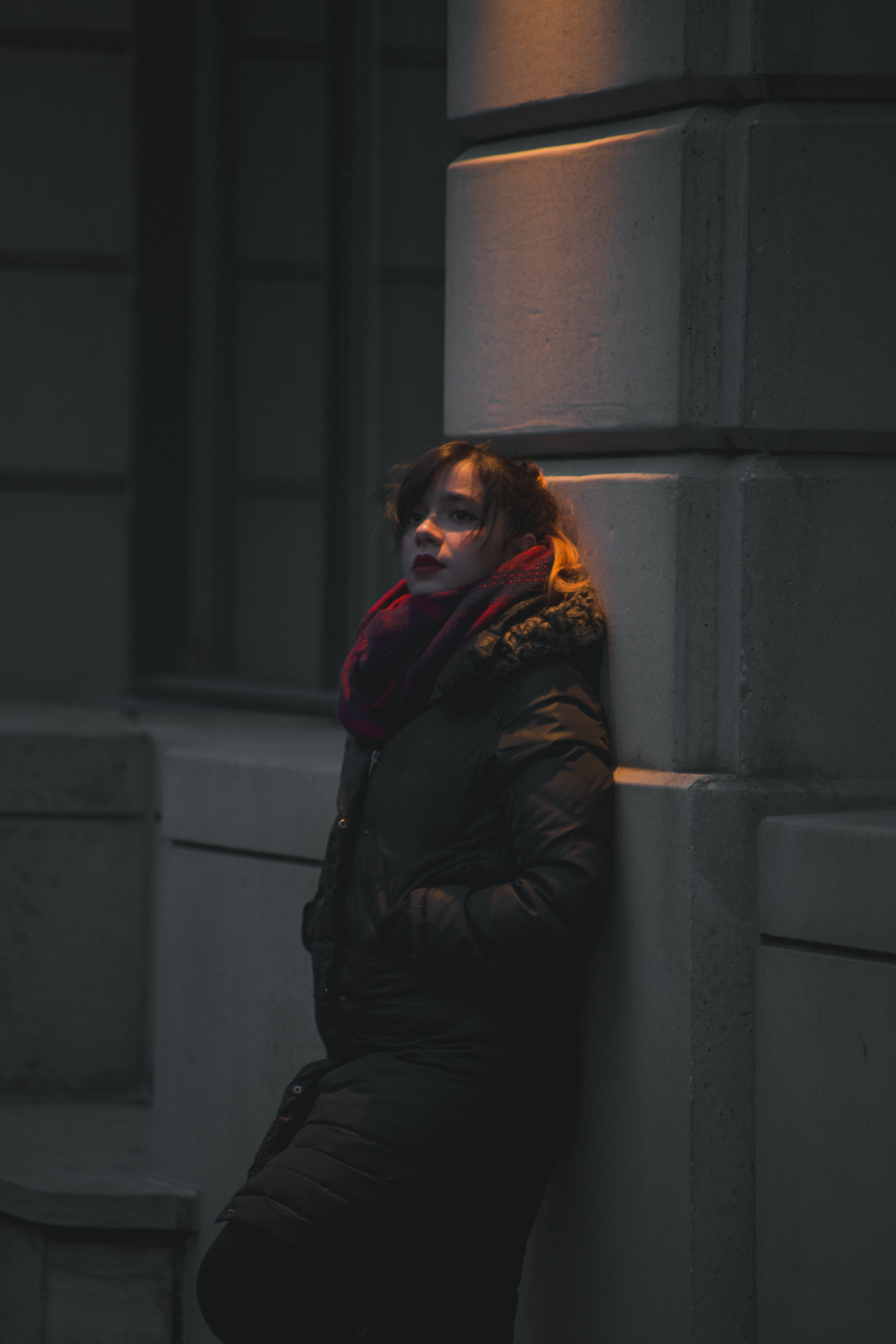woman in black bubble jacket leaning on gray wall during nighttime