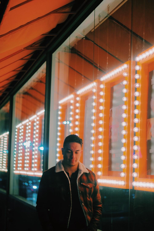 man wearing brown zip-up jacket standing beside clear glass wall
