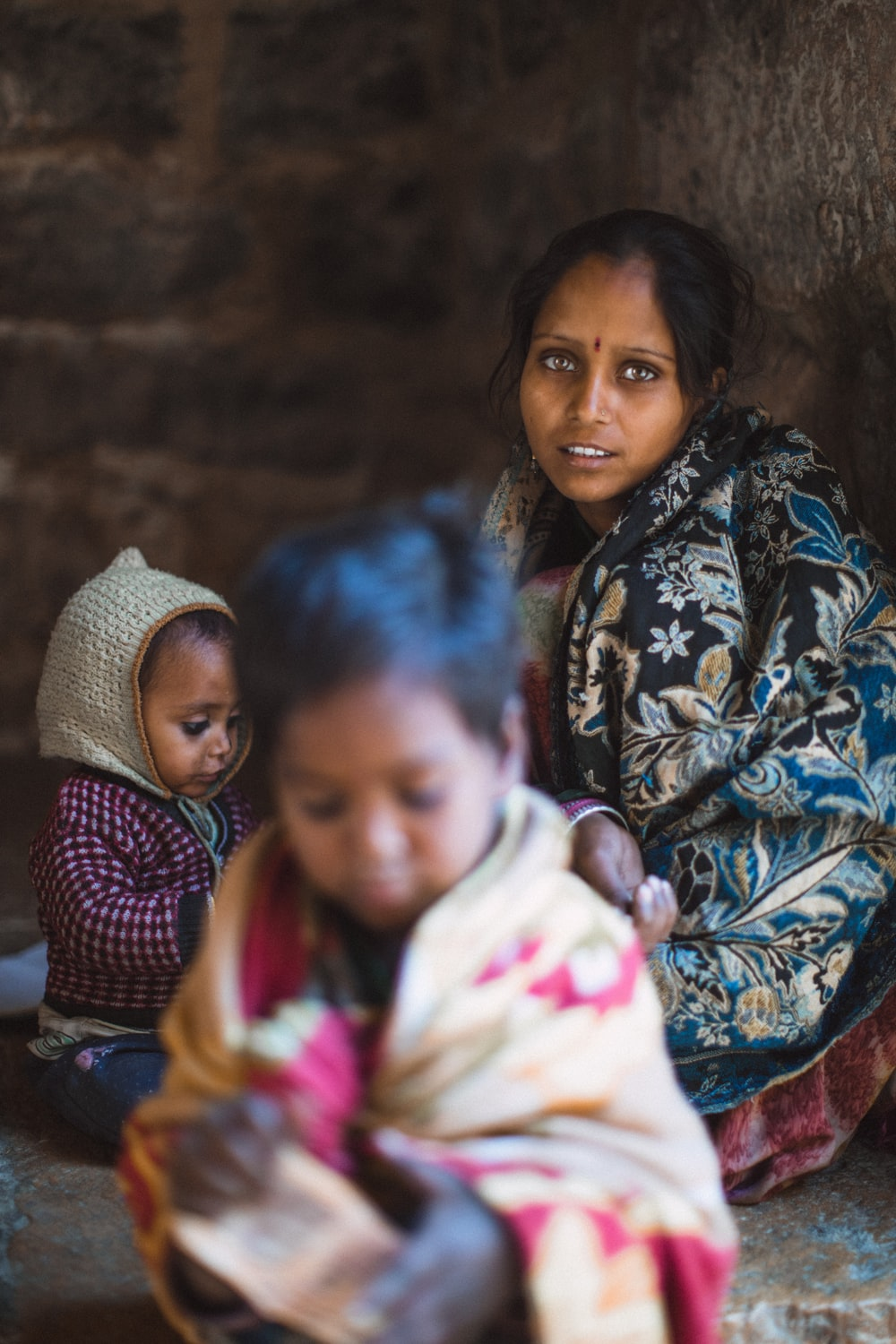 focus photography of woman sitting besides two toddlers