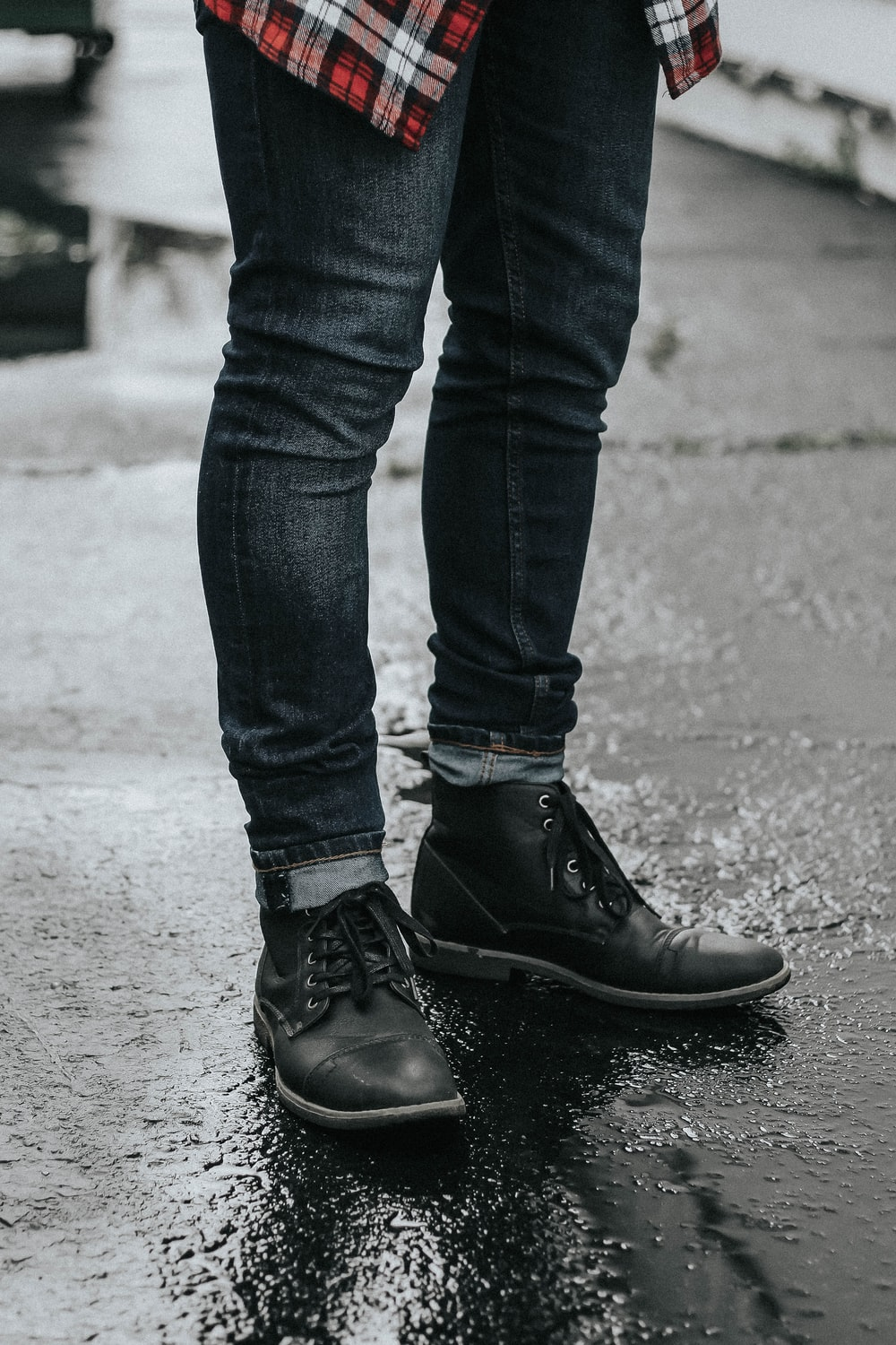 person wearing black denim jeans and pair of black leather boots