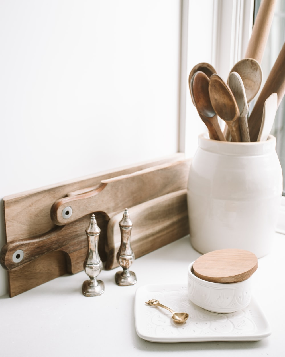 brown wooden spoons on ceramic canister on white top surface