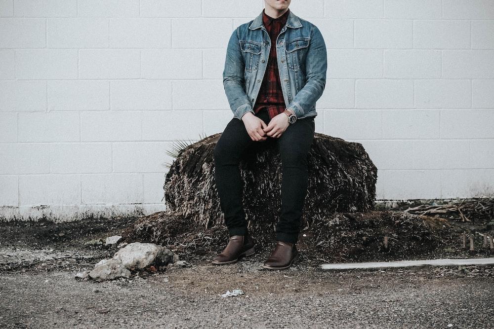 man wearing blue denim western shirt sitting next to white concrete wall