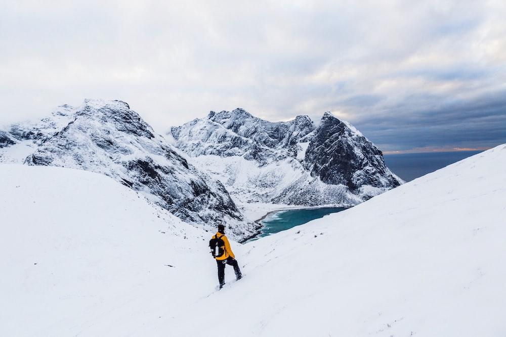 man wearing yellow jacket standing on white snowland at daytime