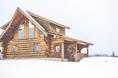 brown wooden house covered by snow log home zoom background