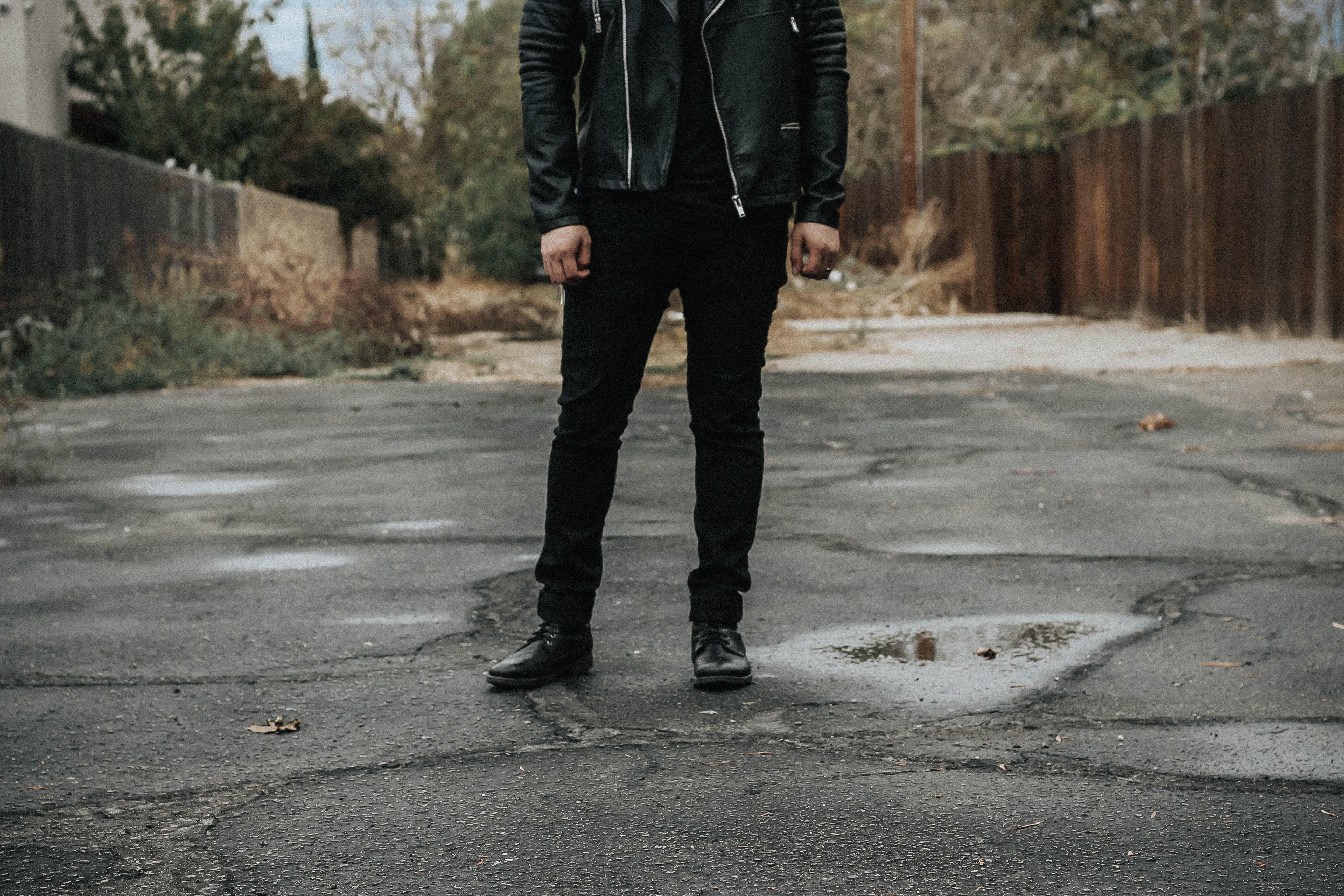 man wearing black pants standing on gray road