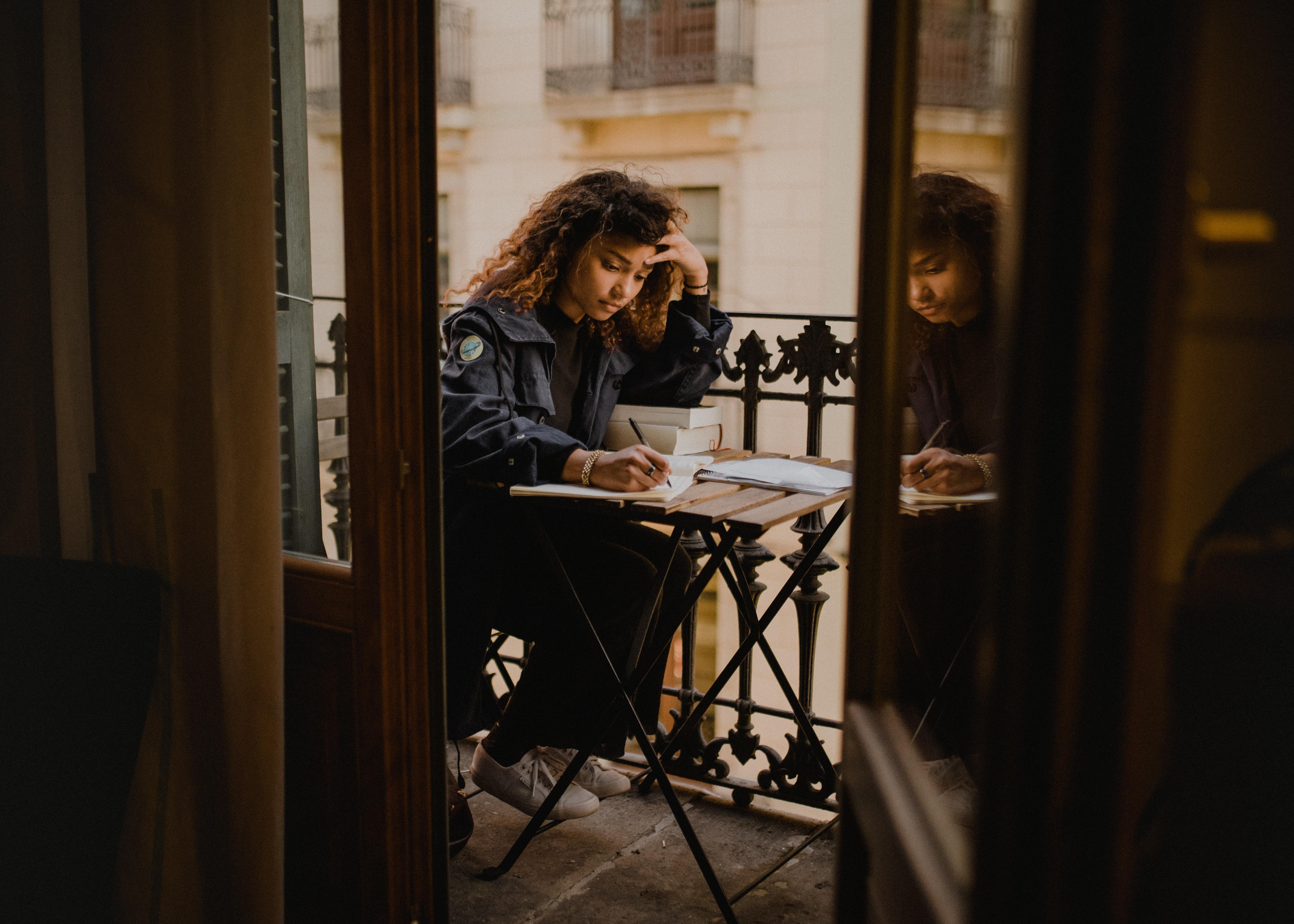 woman wearing black jacket holding pen