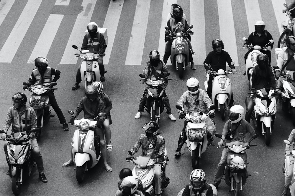 people ride-on motorcycles at the road grayscale photography