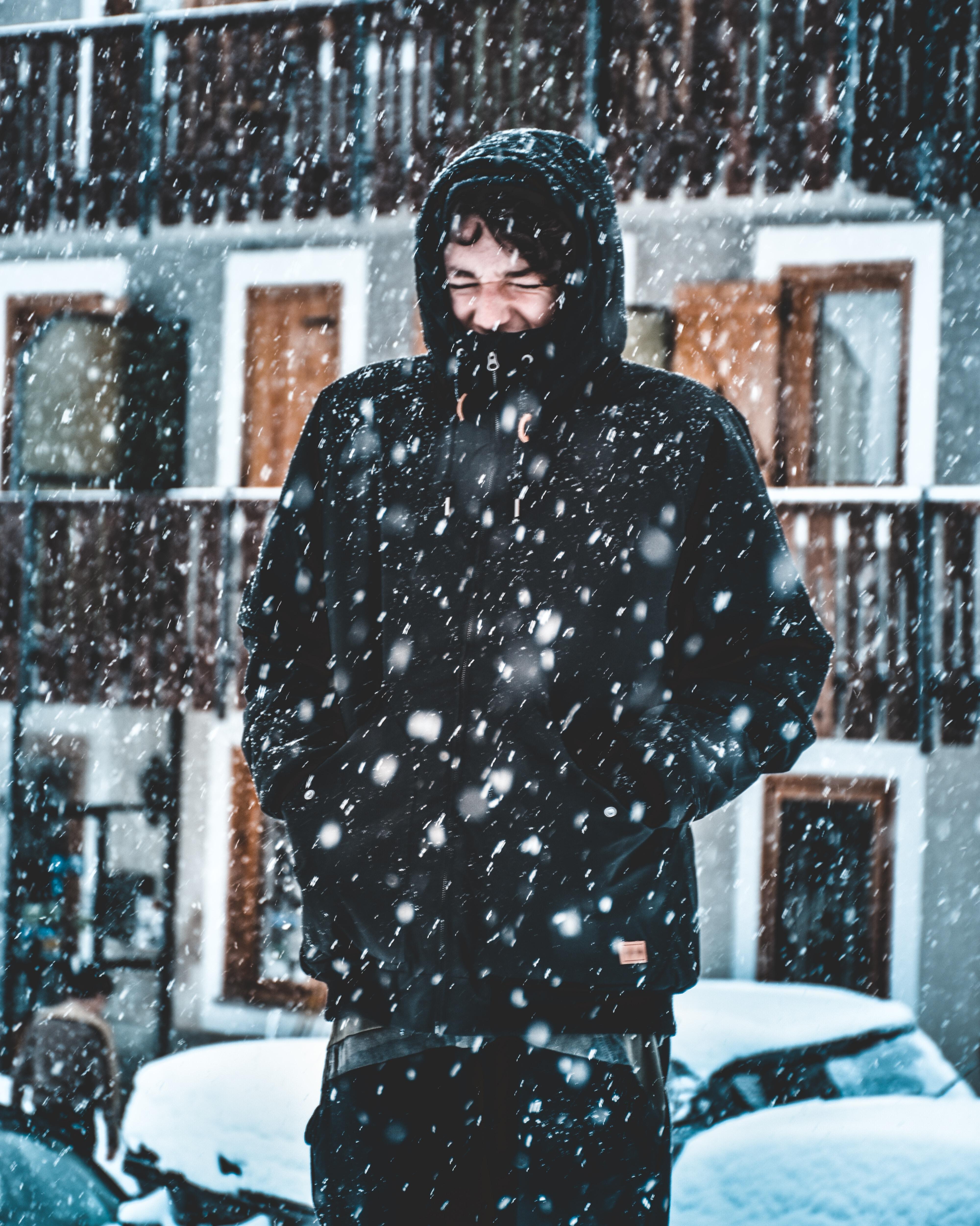 man in black hooded jacket during snow rain