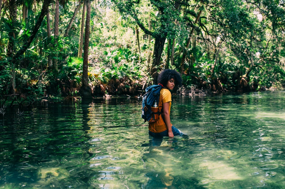 person in orange top wearing backpack walking on body of water in forest during daytime