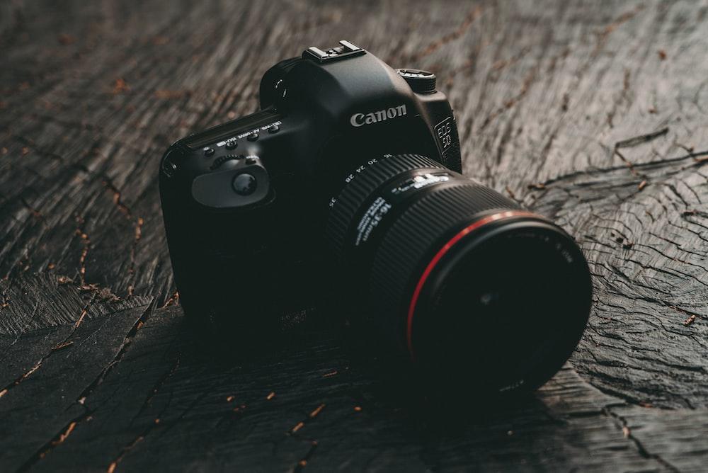 black Canon EOS DSLR camera on brown wooden board