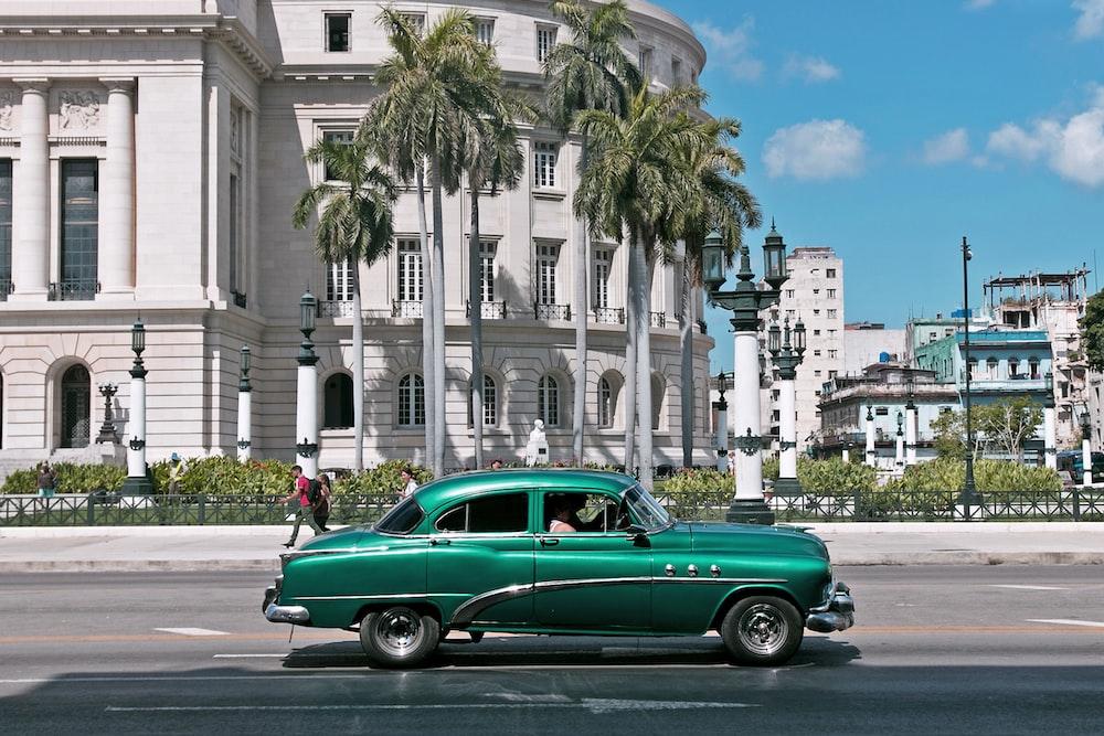 green sedan parks near white building