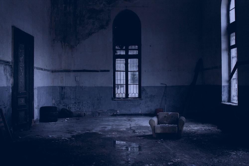 white padded armchair near glass window