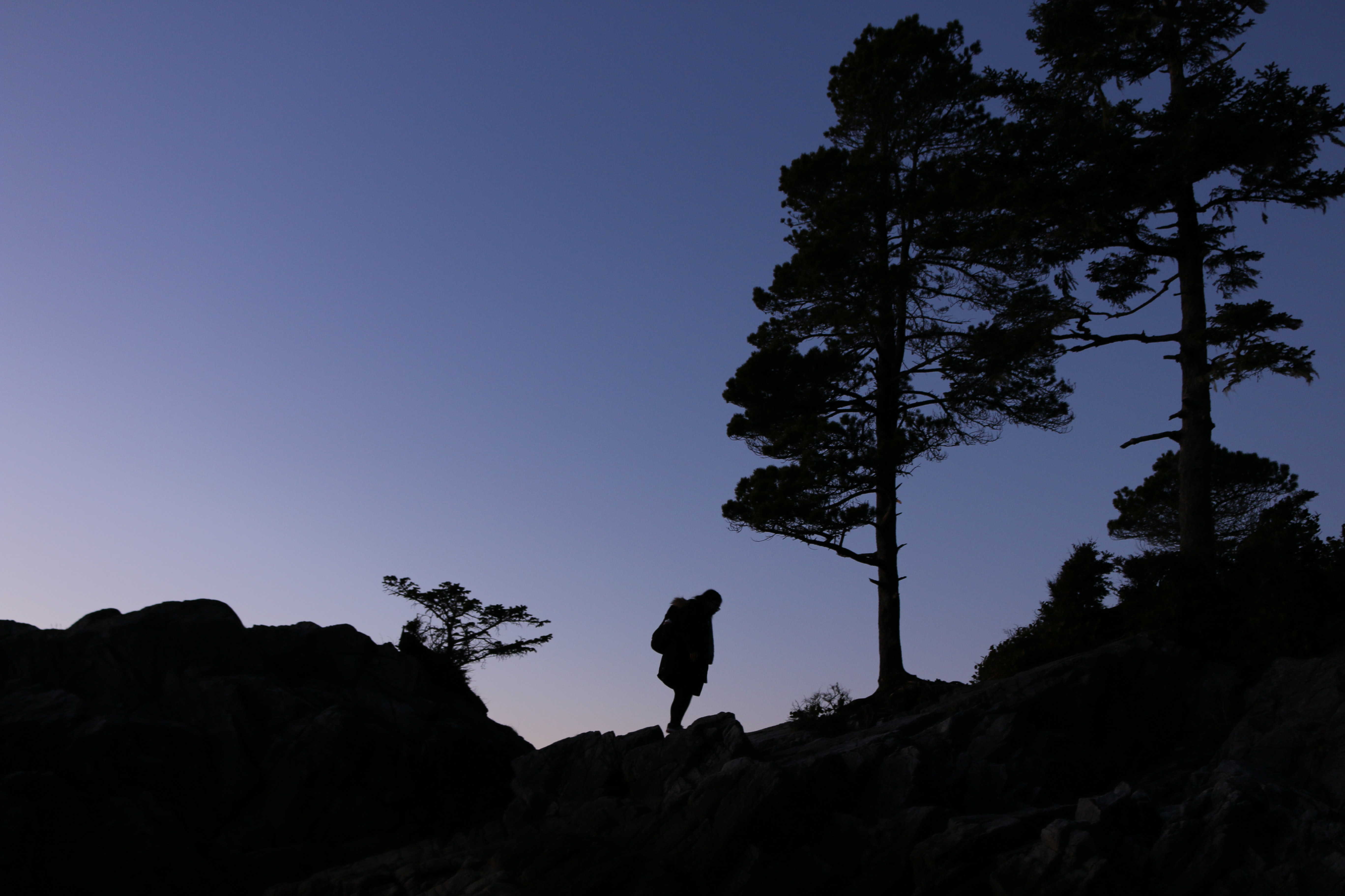 silhouette of person on top of mountain