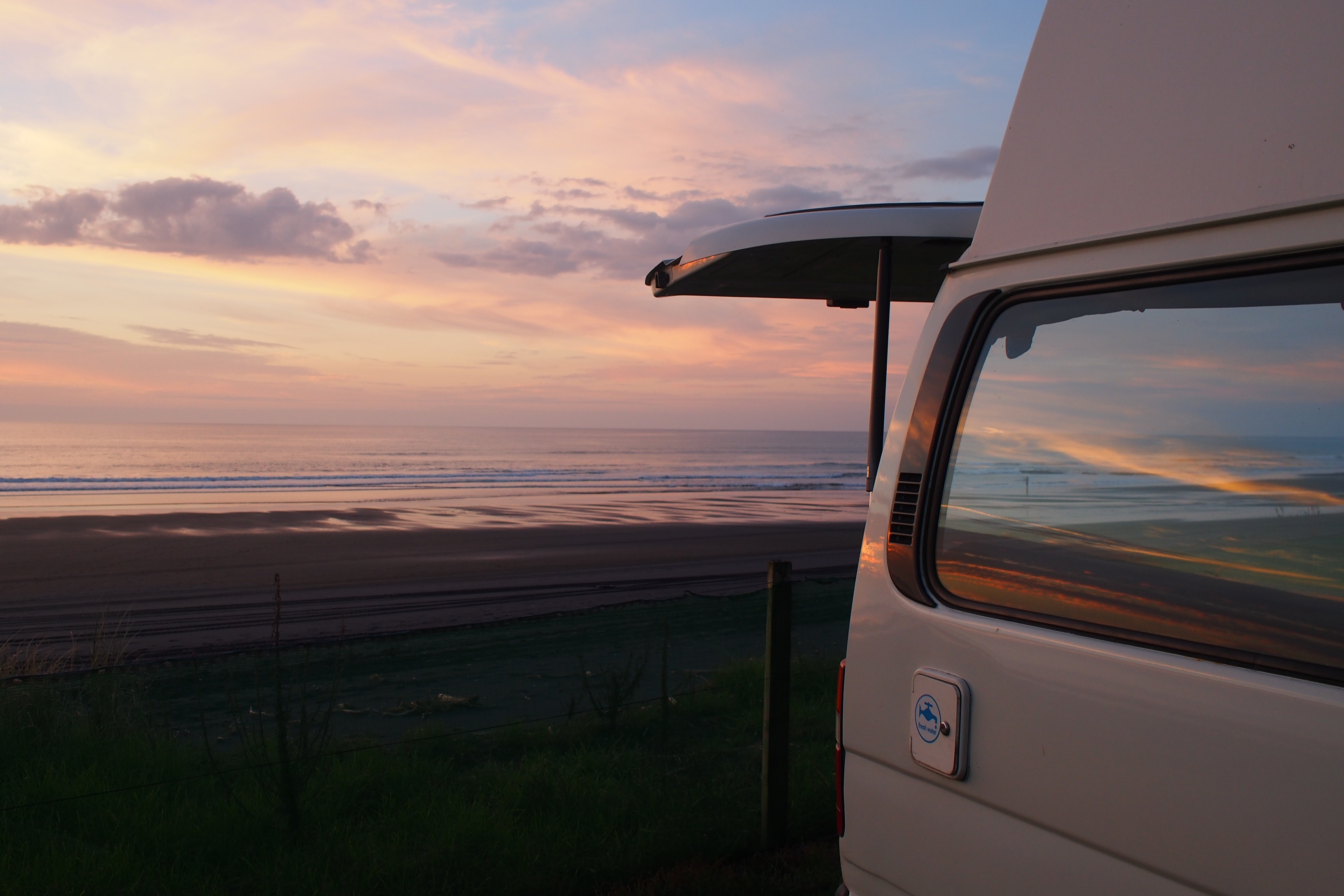 white vehicle parked near ocean during golden hour