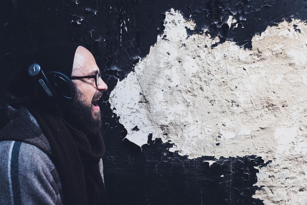 man using headphones shouting beside wall