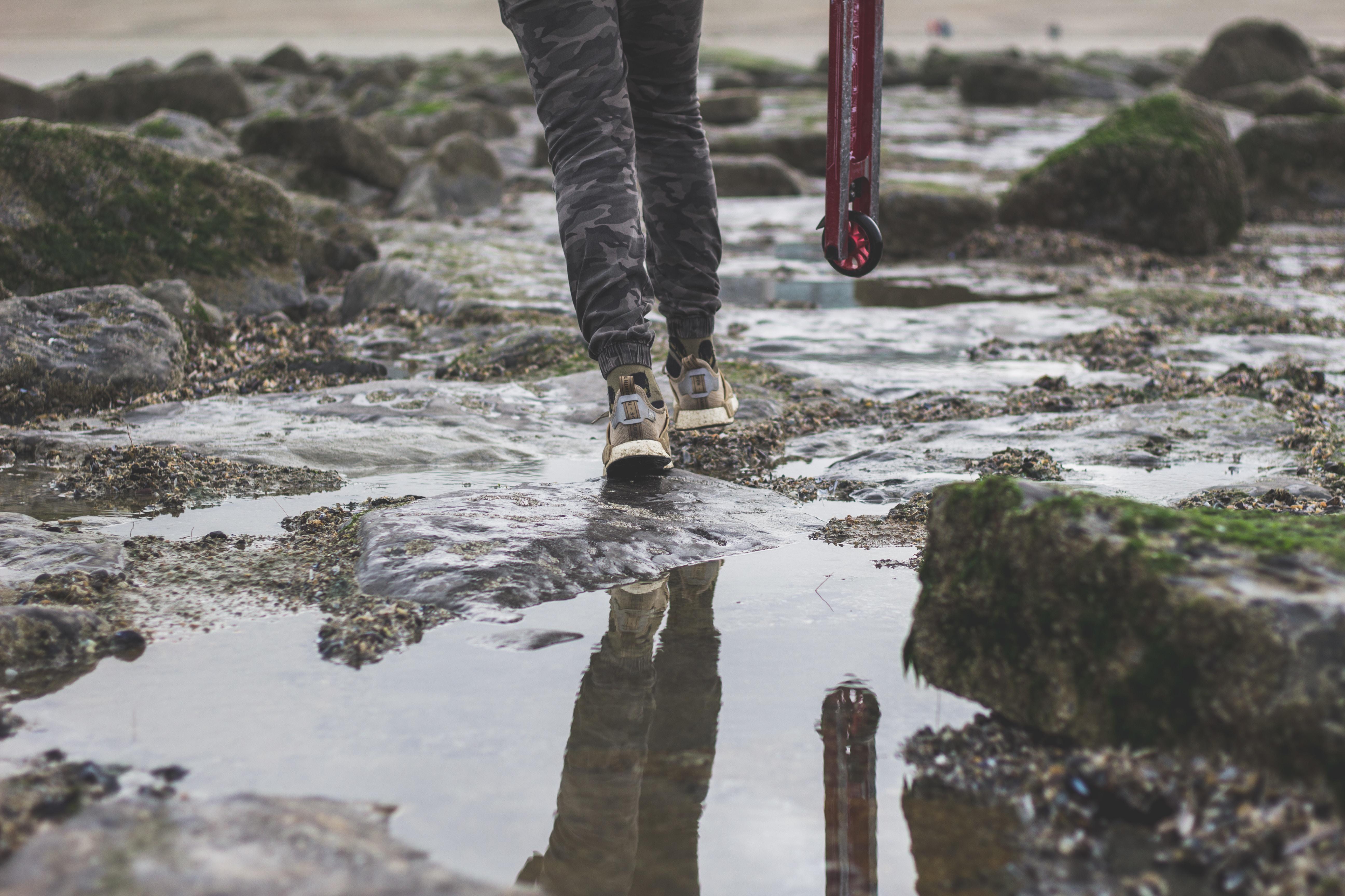 person in gray jeans walking on wet rocks