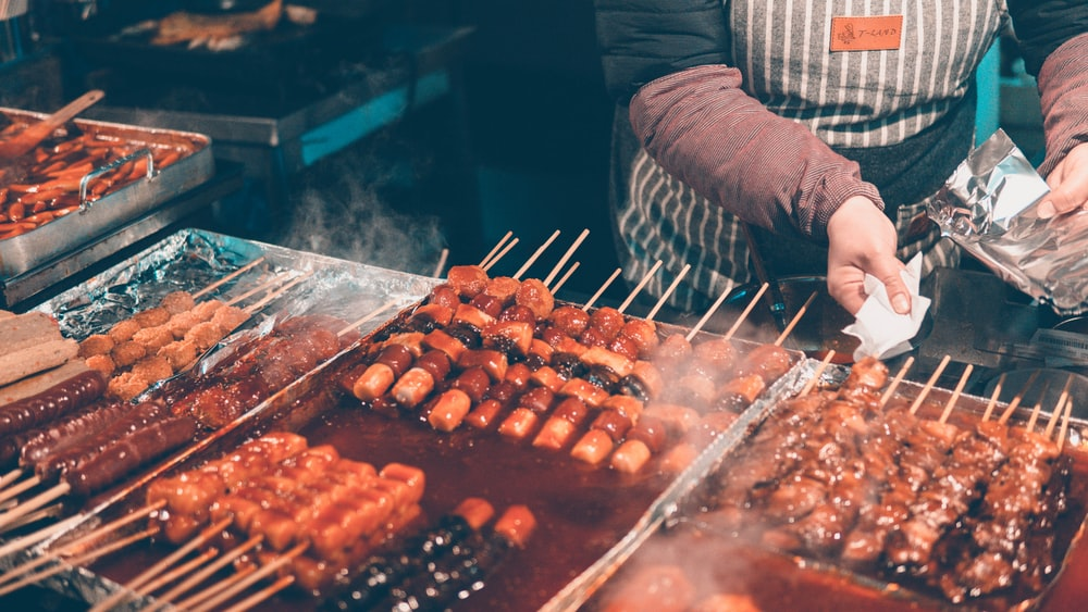 people standing beside skewered food