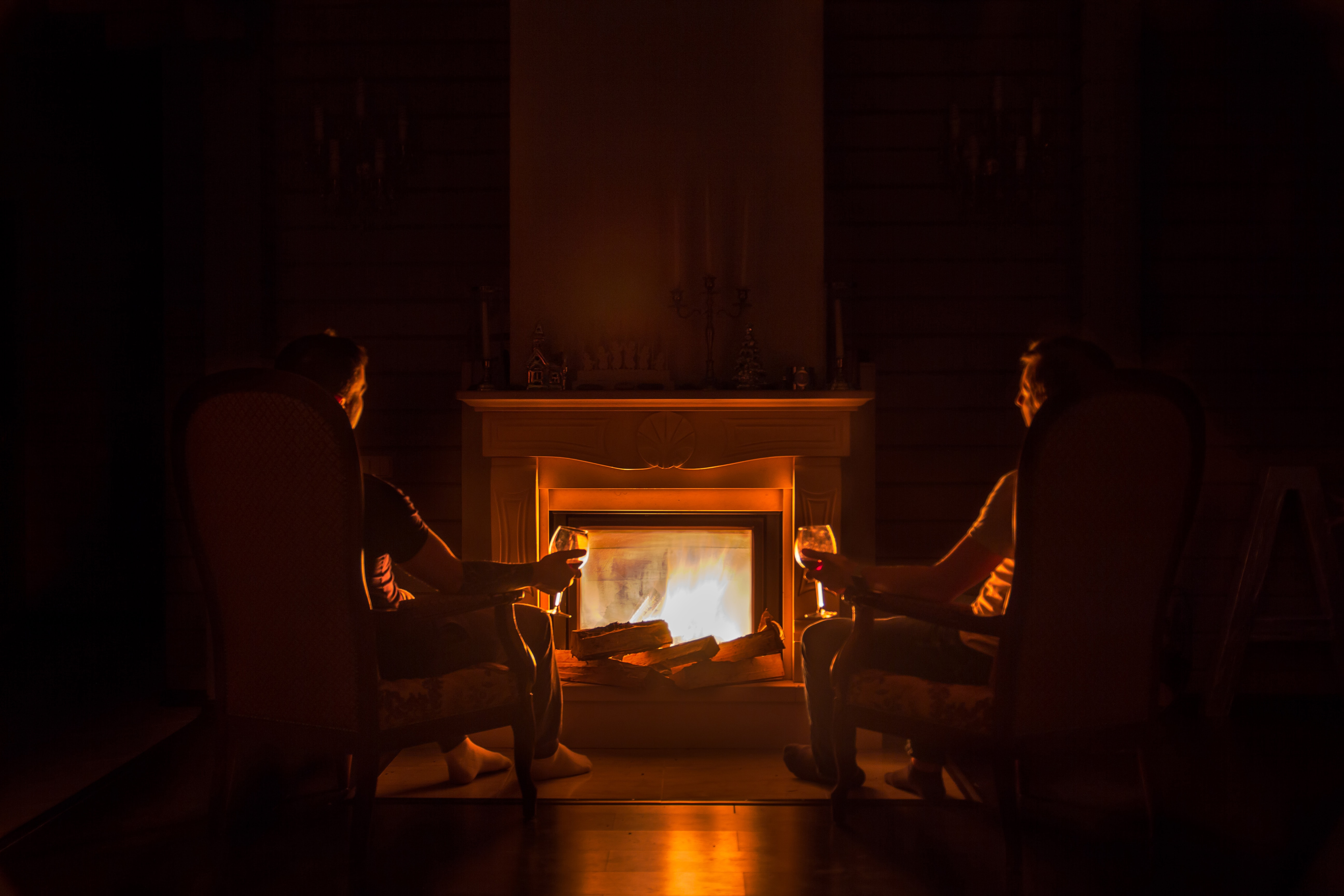 two people sitting in front of fireplace