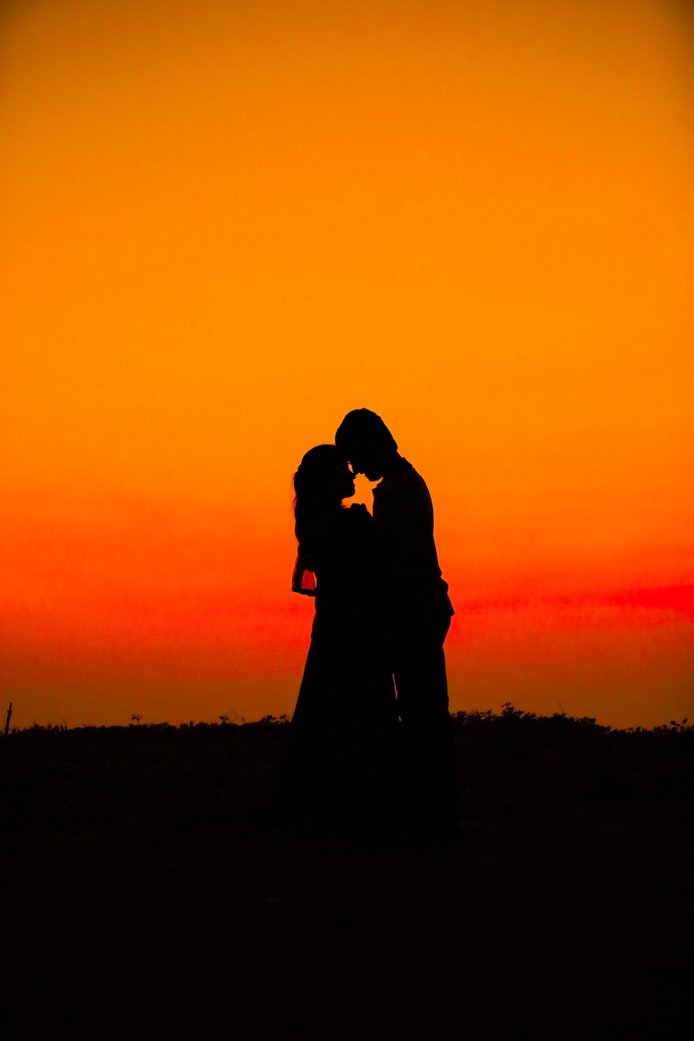 silhouette of man and woman during sunset