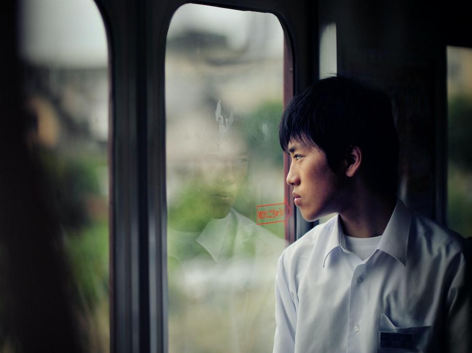Asian man in dress shirt standing in front of glass door