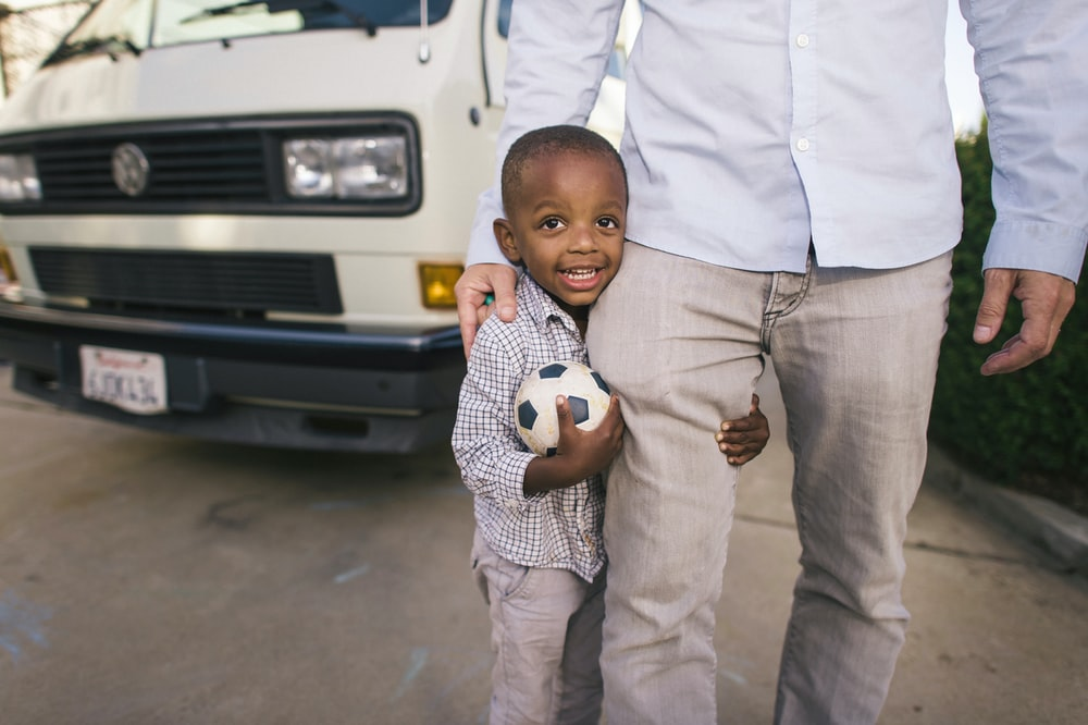 boy standing beside man in white dress shirr near vehicle
