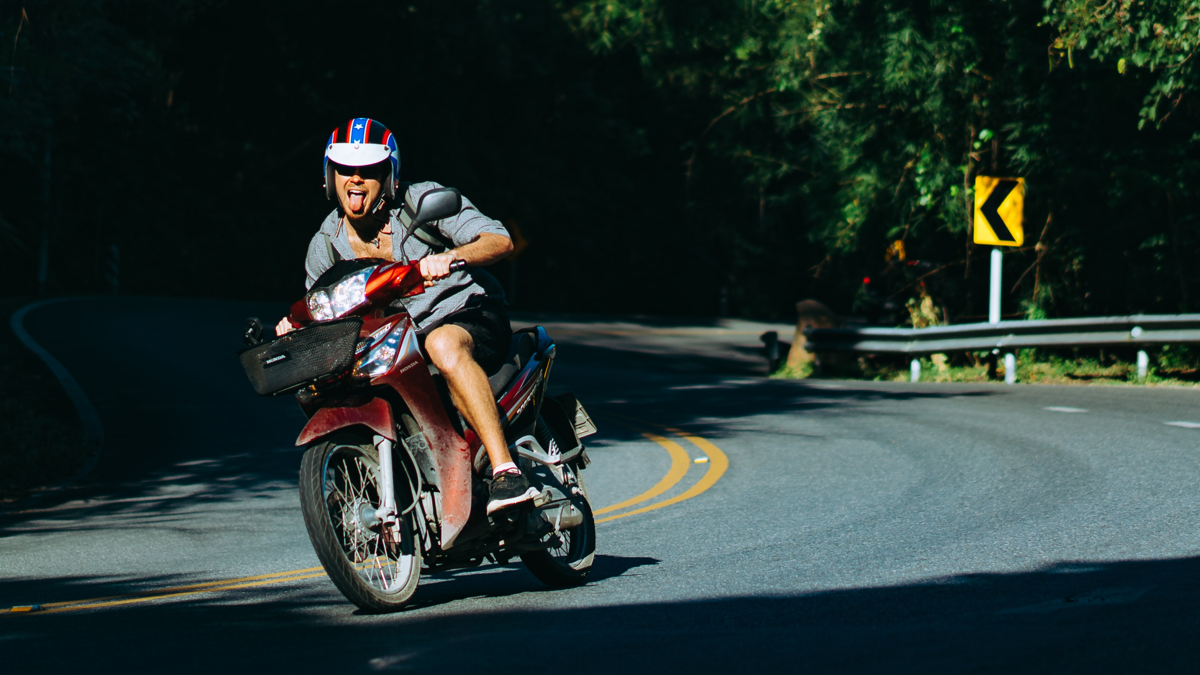 man riding motorcycle on curved road