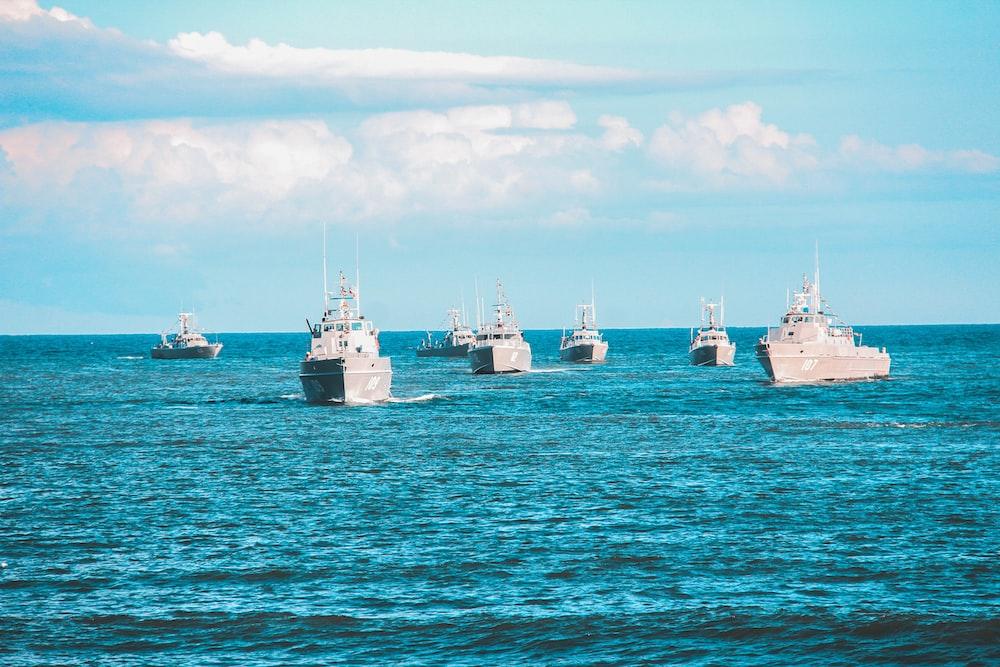 seven navy ship sailing on ocean during daytime