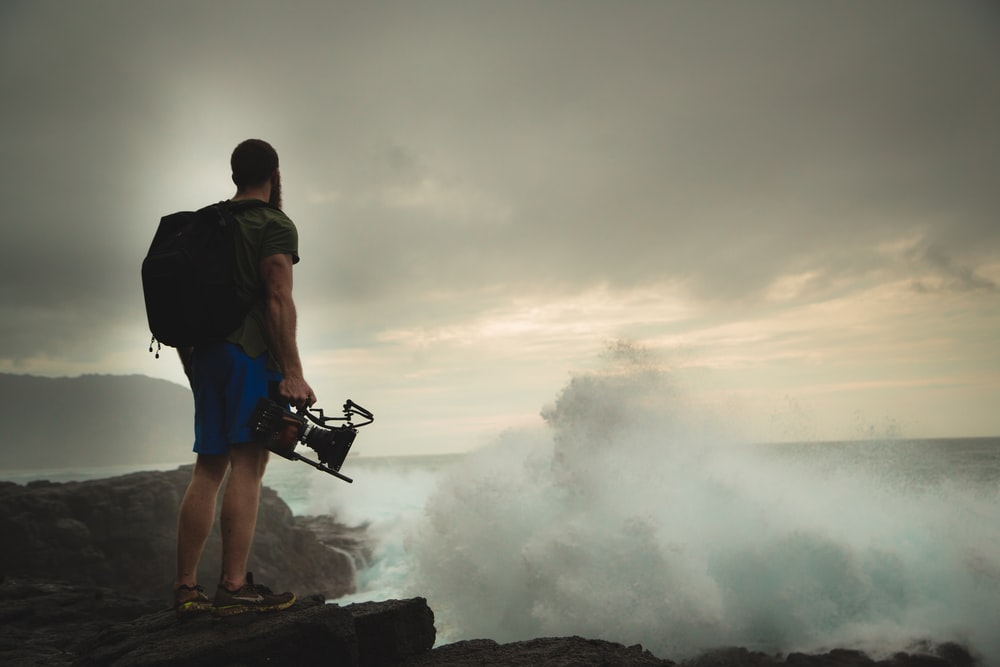 man standing on rock cliff near body of water