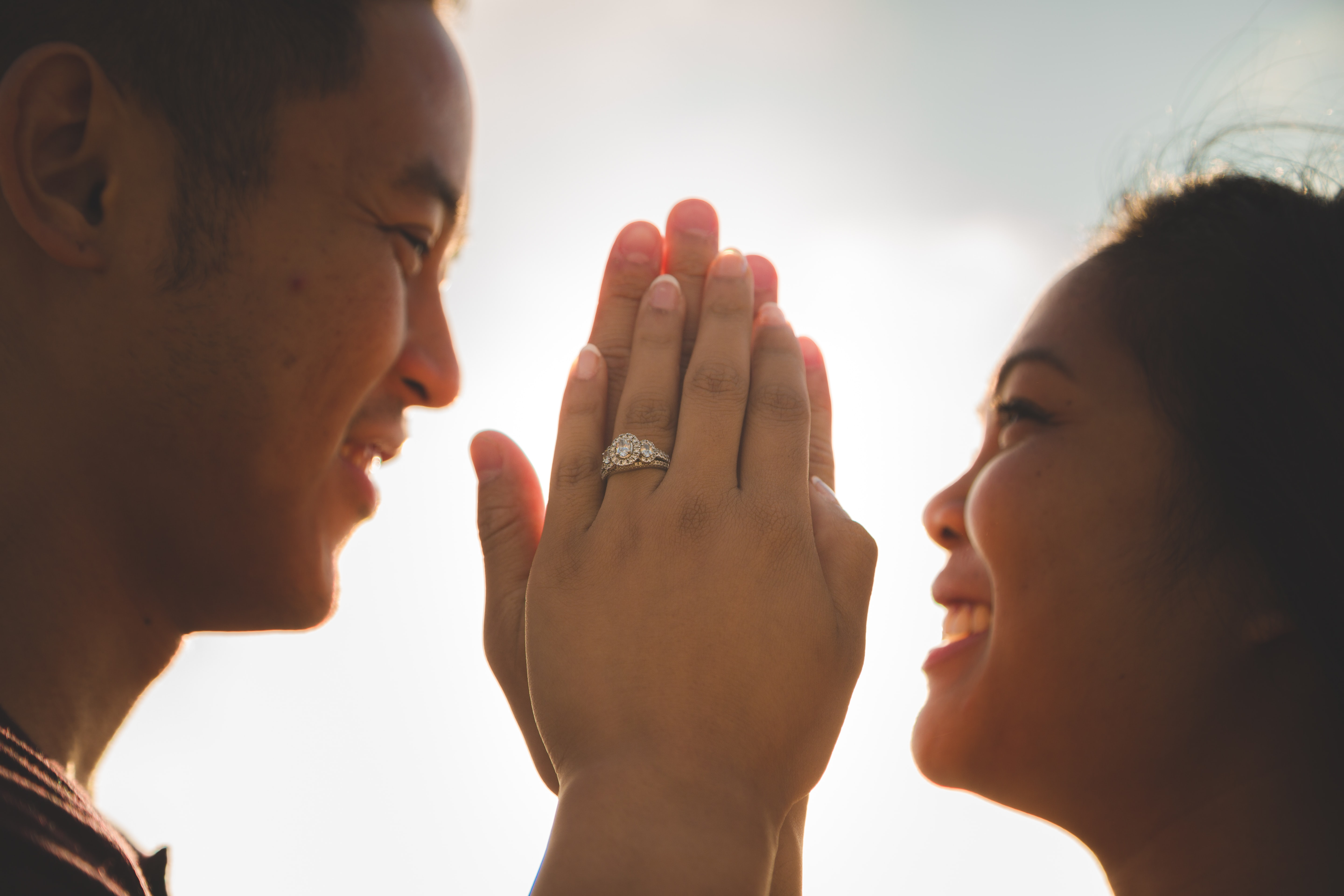 smiling woman and man facing each other while holding palms